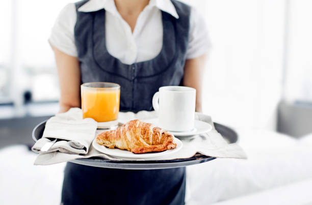 Room service hotel staff carries breakfast tray stock photo