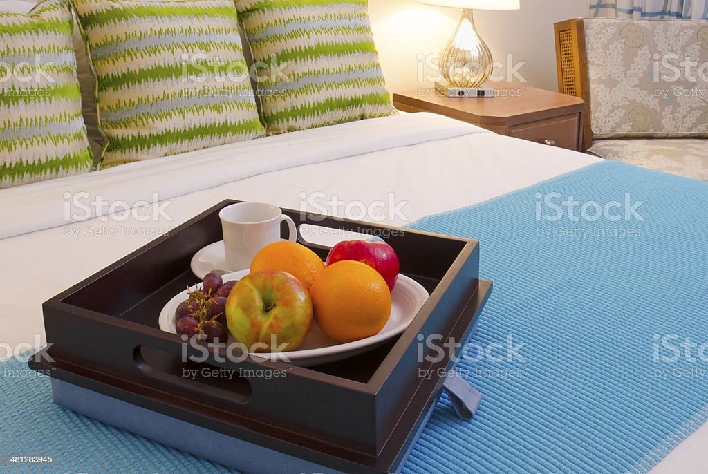 A bed with colorful pillows has a tray filled with fresh fruit.