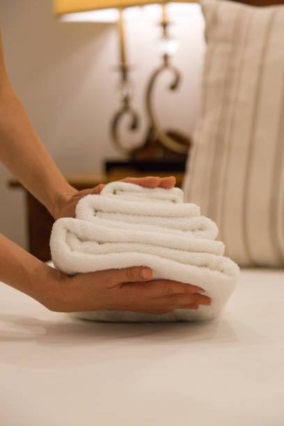 zimmerservice. Frau Wechseltücher im Hotelzimmer. Hausreiniger legt Handtücher auf das Bett, Vorbereitung alles für Kunden zu bewegen – Foto