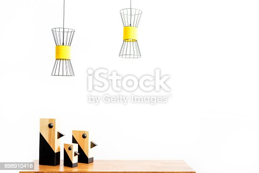 istock Room setting statuettes on table and ceiling lamps over them 698910416