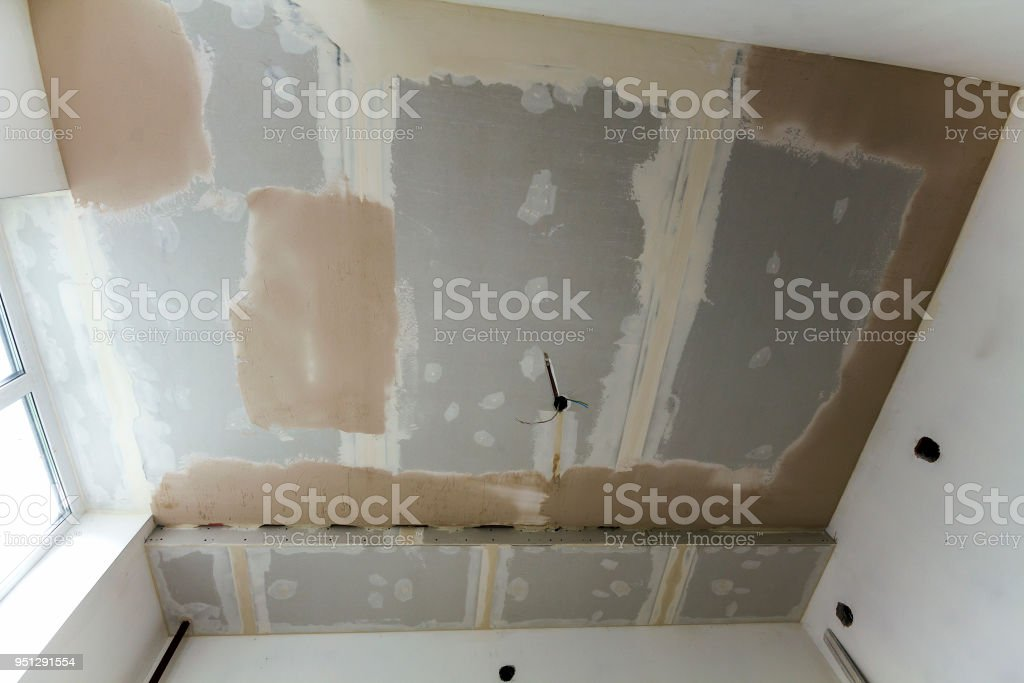 Room under repair or building of new house or apartement. Suspended rough white ceiling of drywall not finished with spots of plaster and electrical cords for bulbs. stock photo
