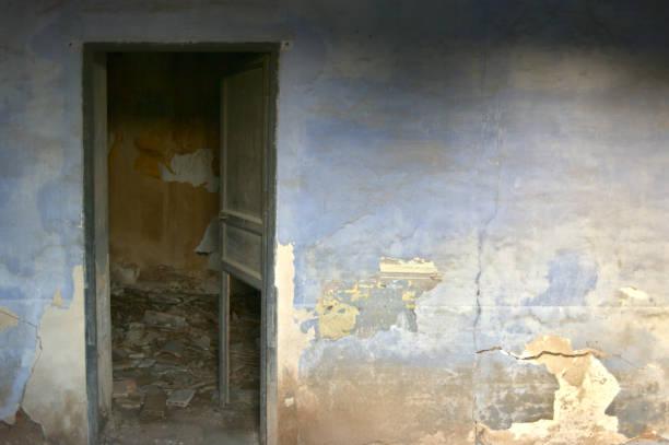 pared de la habitación con pintura deteriorada y puerta abierta - foto de stock