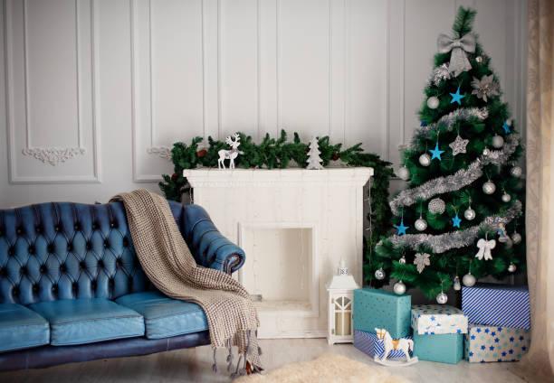 Zimmer mit einem Weihnachtsbaum und einem weißen Kamin am Kamin – Foto