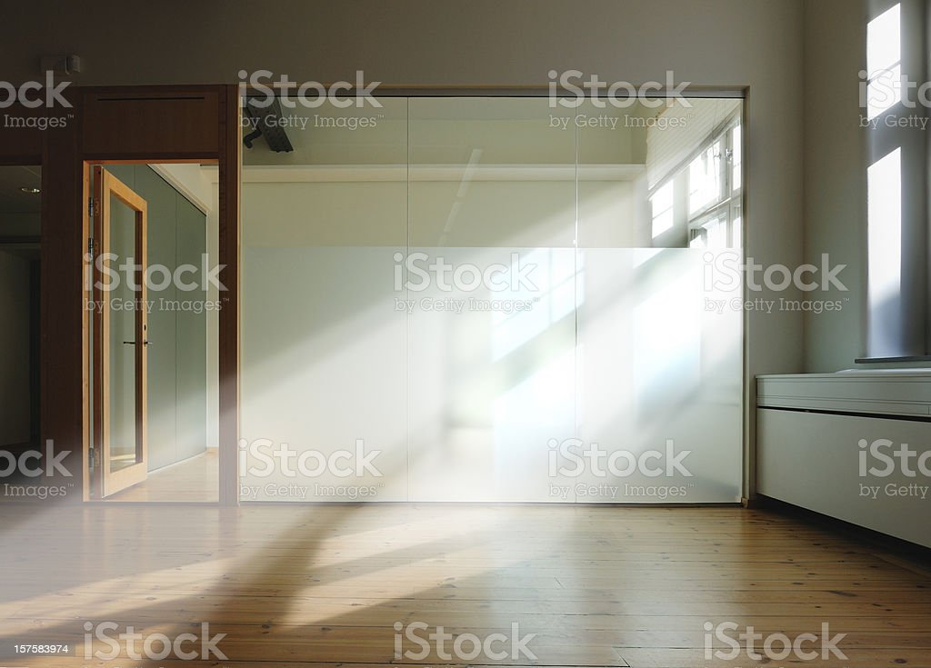 Room with beams of sunlight through glass wall stock photo