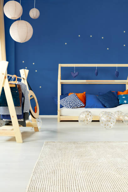 zimmer mit bett und coat rack - marineblau schlafzimmer stock-fotos und bilder