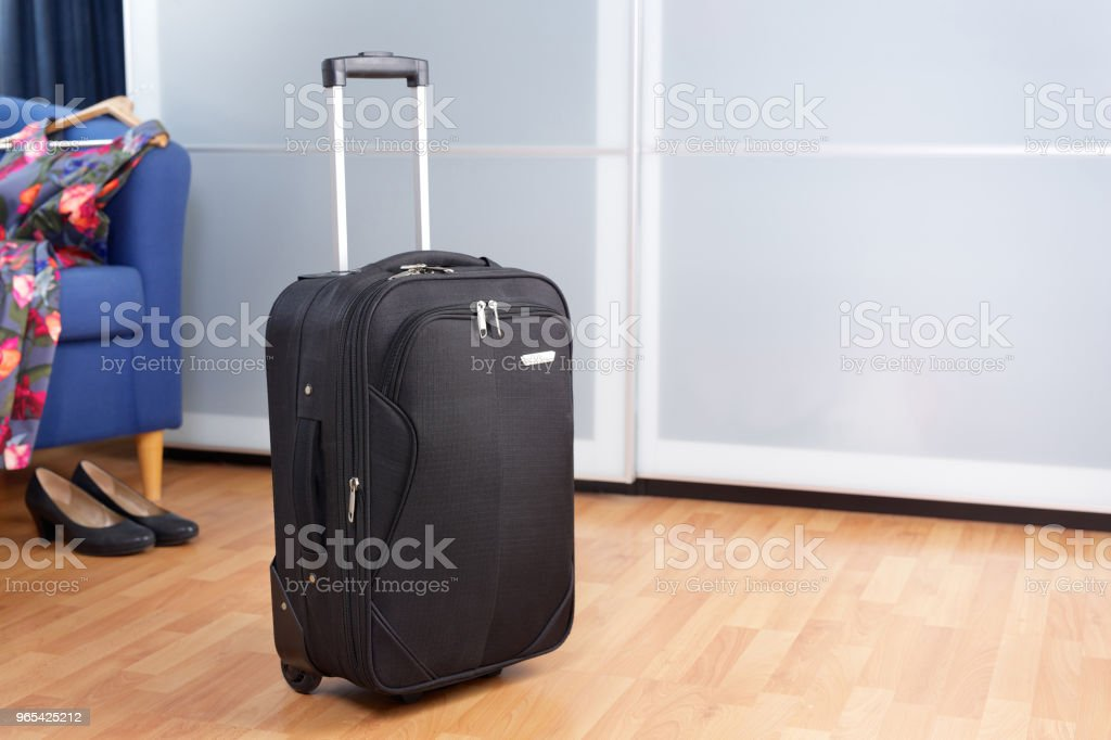 Room with black packed roller suitcase in front of closet zbiór zdjęć royalty-free