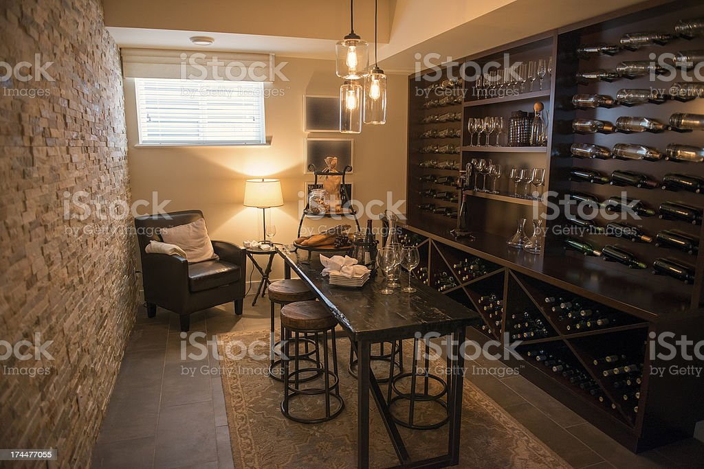 Room with dark dining furniture and wine filled shelves stock photo
