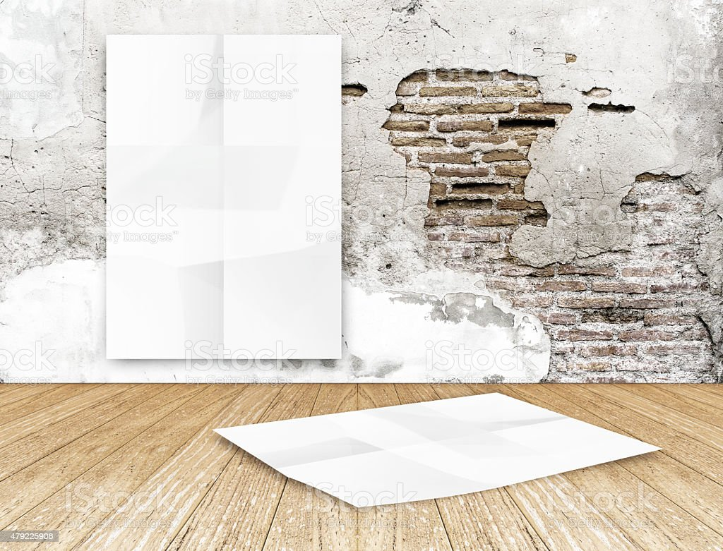 room with hanging blank crumpled white poster at crack brick stock photo