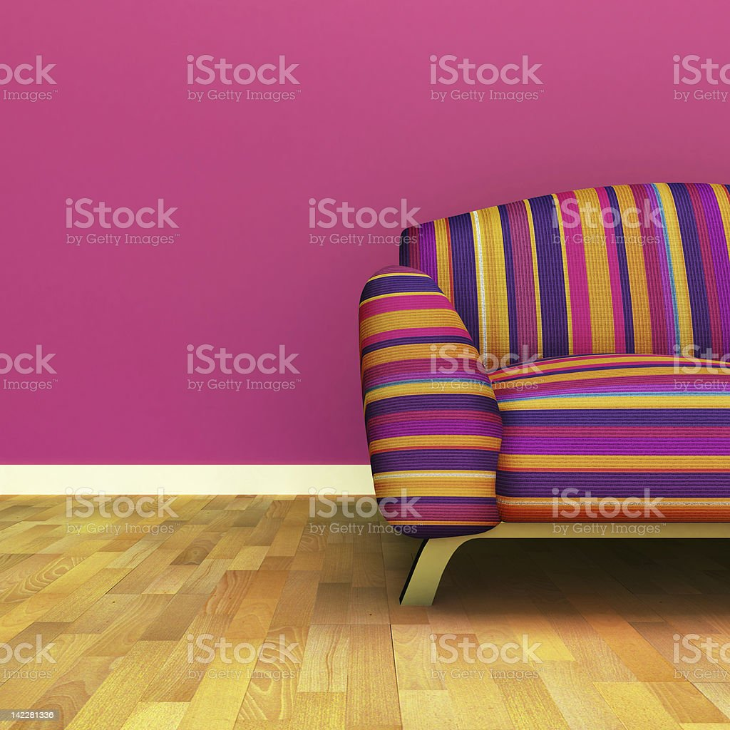 Room with multicolored couch, pink wall, and wood floors stock photo