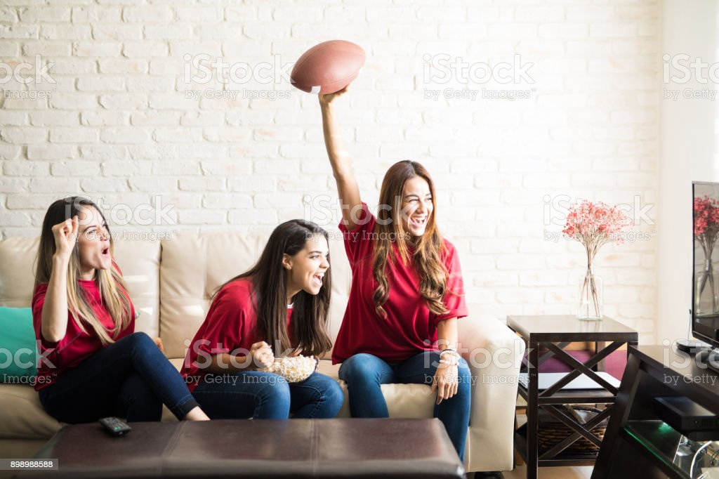 Roomies watching a football game stock photo