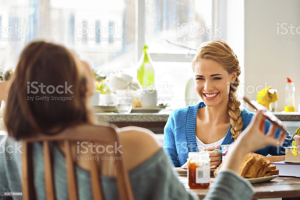 Roommates eating breakfast Cheerful female roommates sitting at the kitchen table, eating breakfast and talking. 20-24 Years Stock Photo