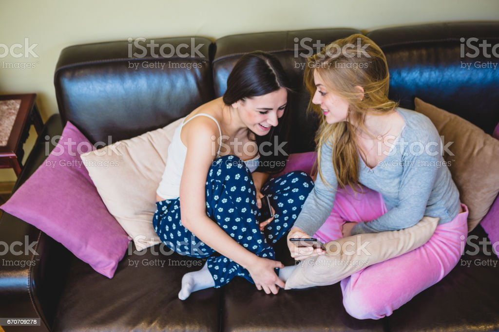 Roommates, lesbian student couple chating, having fun in their livingroom  on leather sofa - Stock image .