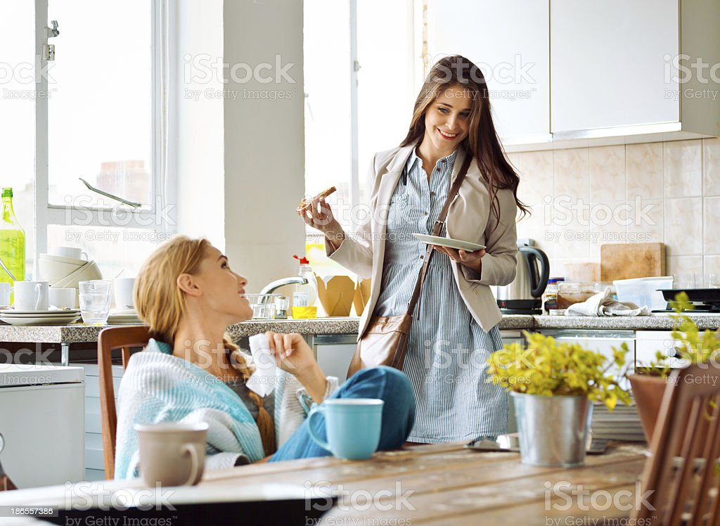 Roommates, Lifestyle Young woman sitting in a kitchen wrapped in blanket and talking with her friend eating tost in a hurry. 20-24 Years Stock Photo