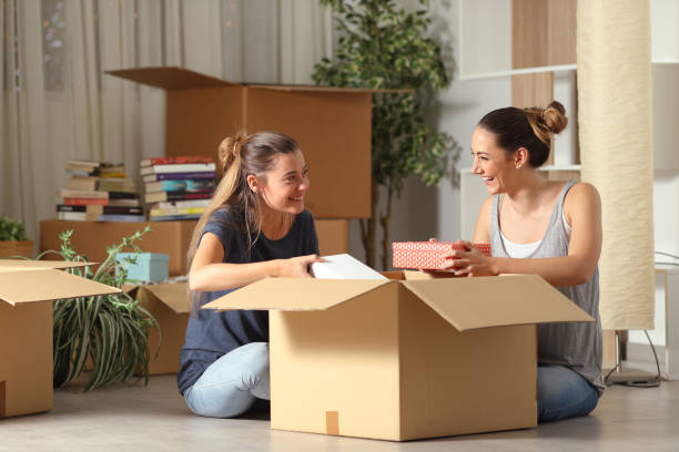 roommates talking unboxing gelongings moving home - oggetti personali foto e immagini stock