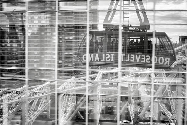 roosevelt island cable tramway car reflected in buildings windows. - roosevelt island foto e immagini stock