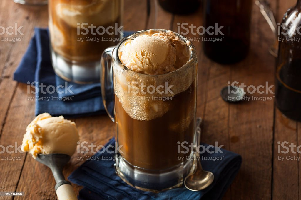 Root beer float in glass mug with scoop on wood table stock photo