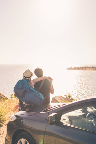 Ropad trip summer love Couple sitting on the car hood with backpacks and bags on and looking at the beautiful sea view and enjoying time together bonnet stock pictures, royalty-free photos & images