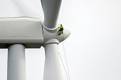 Rope access technicians rappelling down to working on blade of wind turbine and preparing rope protectors on the rope.