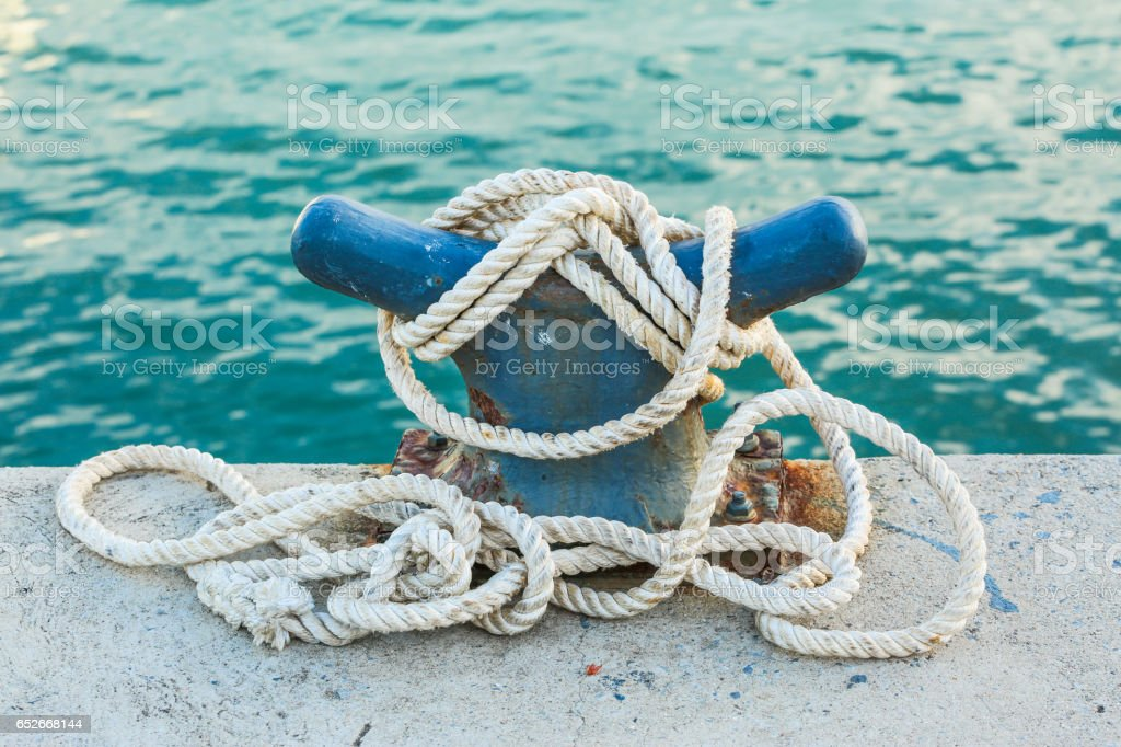Rope and a jetty cleat with sunlight stock photo