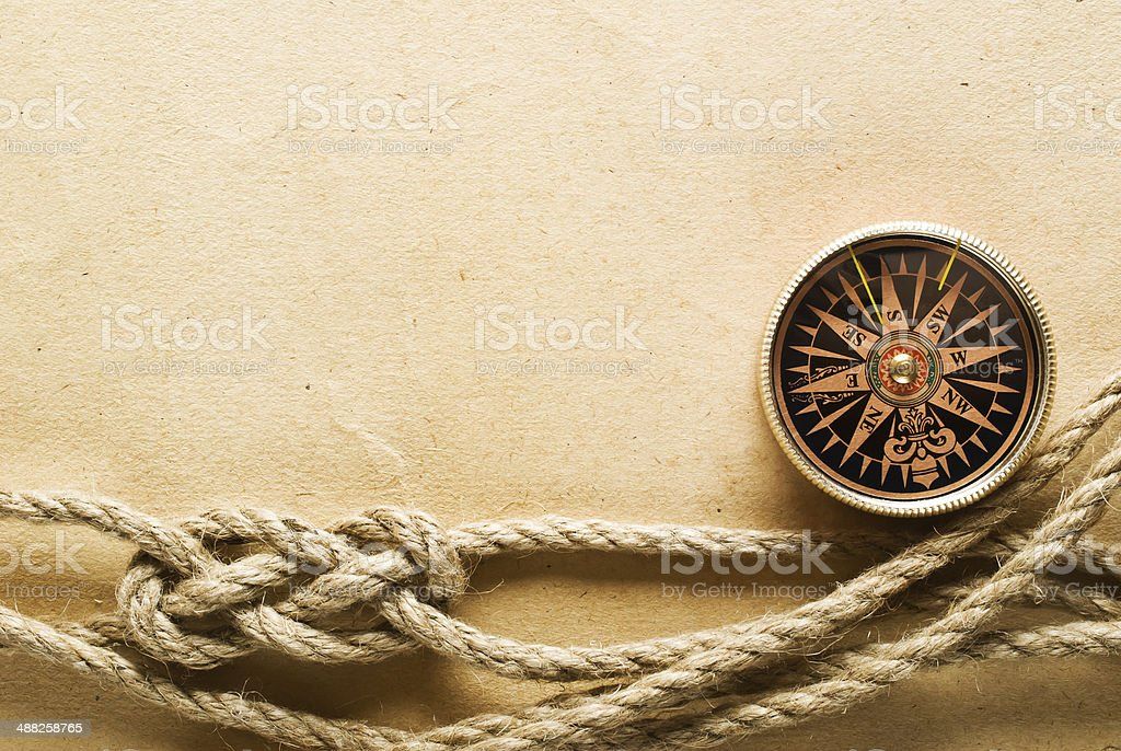 Rope and compass on the old paper background stock photo
