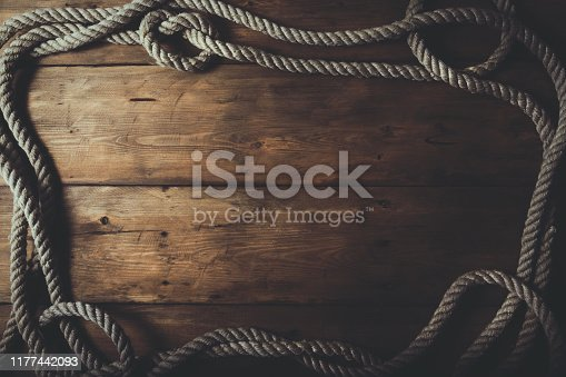 rope frame on old brown wooden plank background