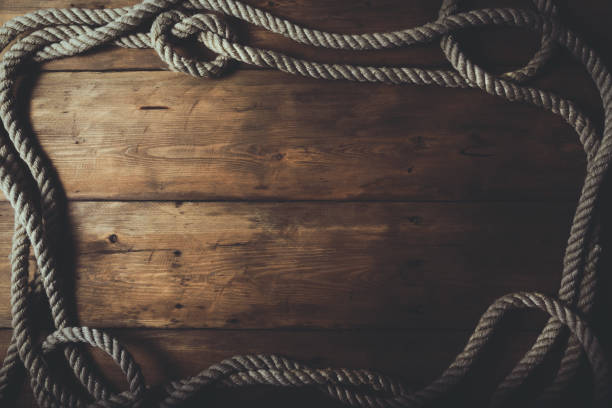 rope frame on old brown wooden plank background stock photo