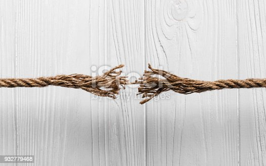 istock Rope frayed about to break on Wooden background 932779468