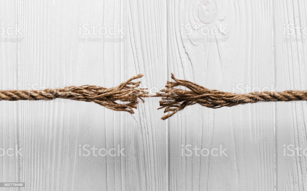 Rope frayed about to break on Wooden background stock photo