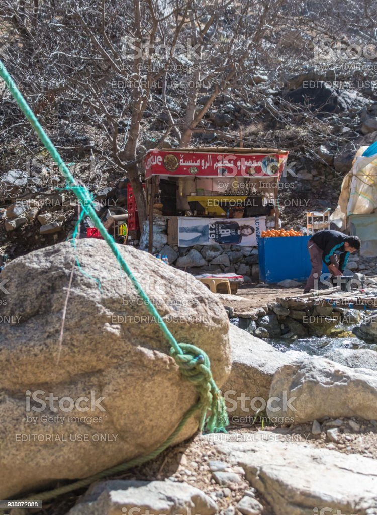 Rope held by a boulder with a drinks stall in Atlas Mountains, Morocco stock photo