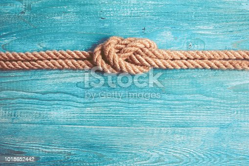 Rope, knot and wooden background