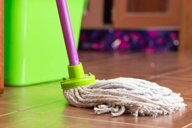 Rope mop for cleaning the floor on the background of a plastic bucket Rope mop for cleaning the floor on the background of a plastic bucket. Close-up, selective focus, green plastic bucket mop stock pictures, royalty-free photos & images