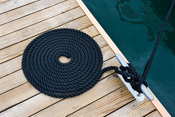rope of yacht Black yacht's rope on dock. mooring stock pictures, royalty-free photos & images