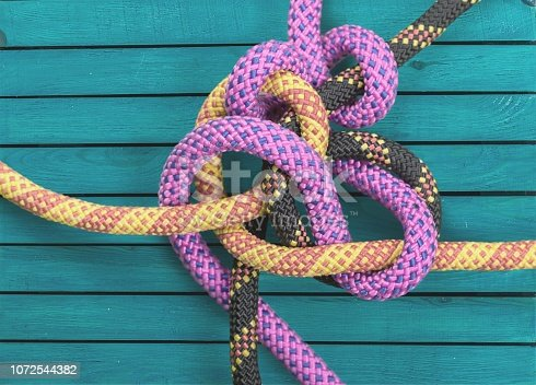 Knot on a colorful cord  on wooden background