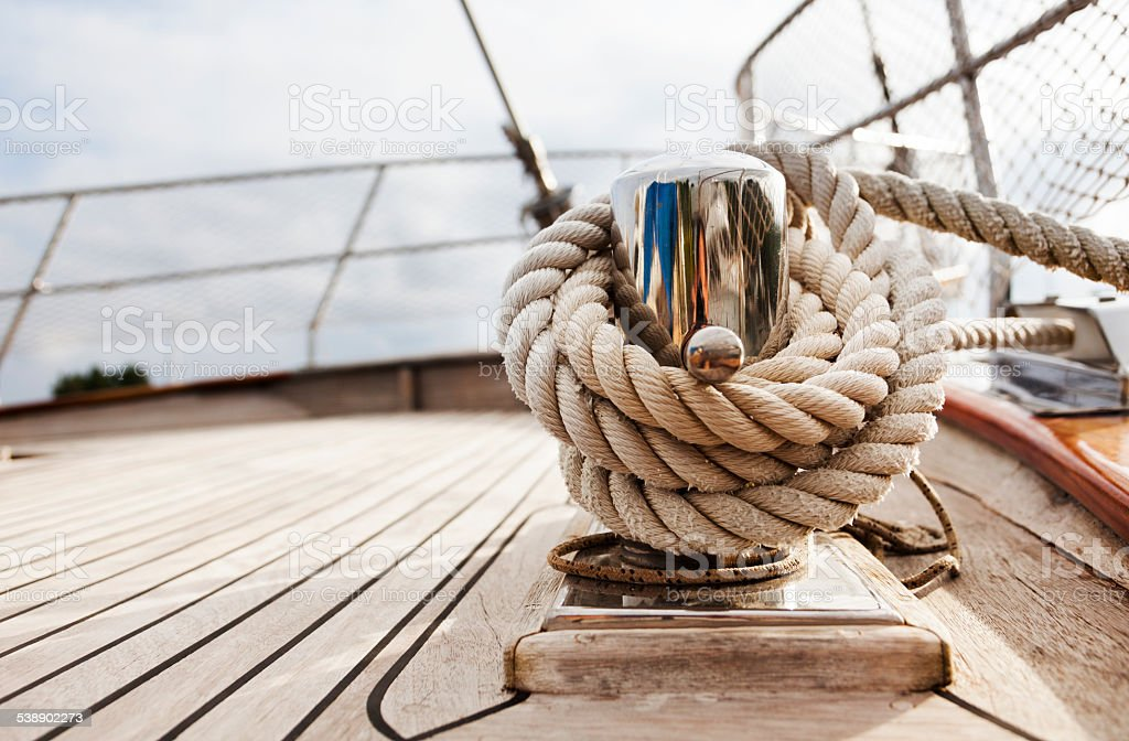 Rope tighten on Cleat. Hawser. Sailing Yacht. Hawser. Deck. Close-up. stock photo