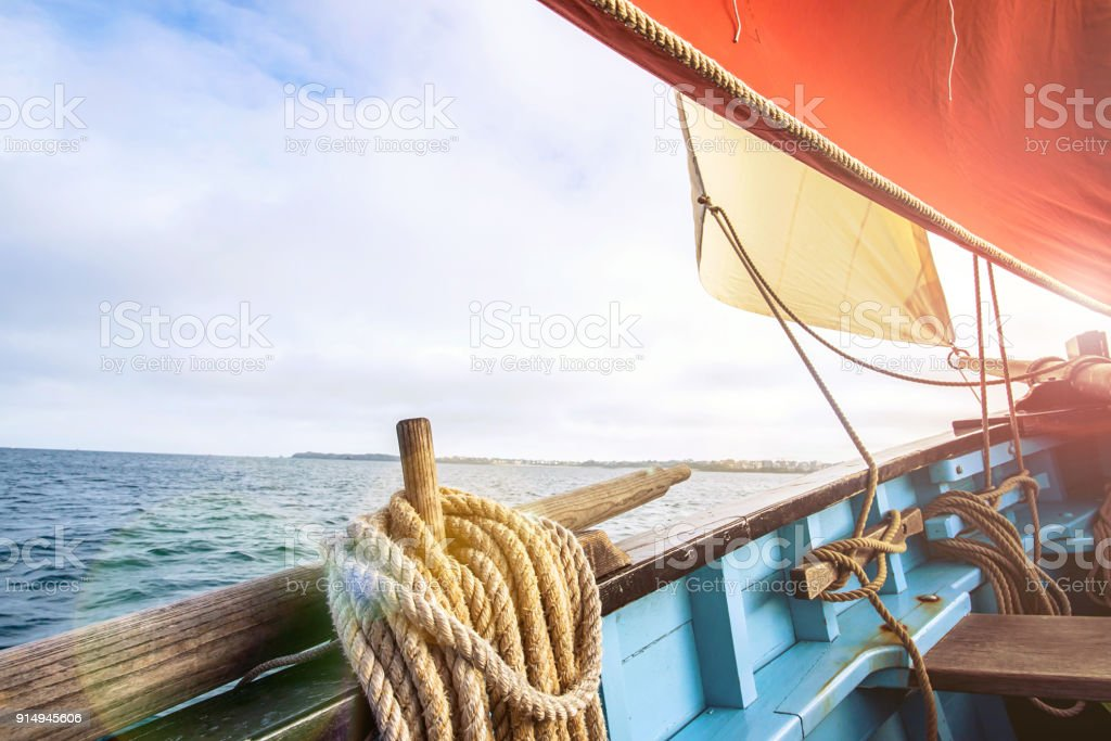rope wound on a wooden cleat fixed on the hull of a rigging vintage sailing boat with a beige jib and an ocher sail stock photo