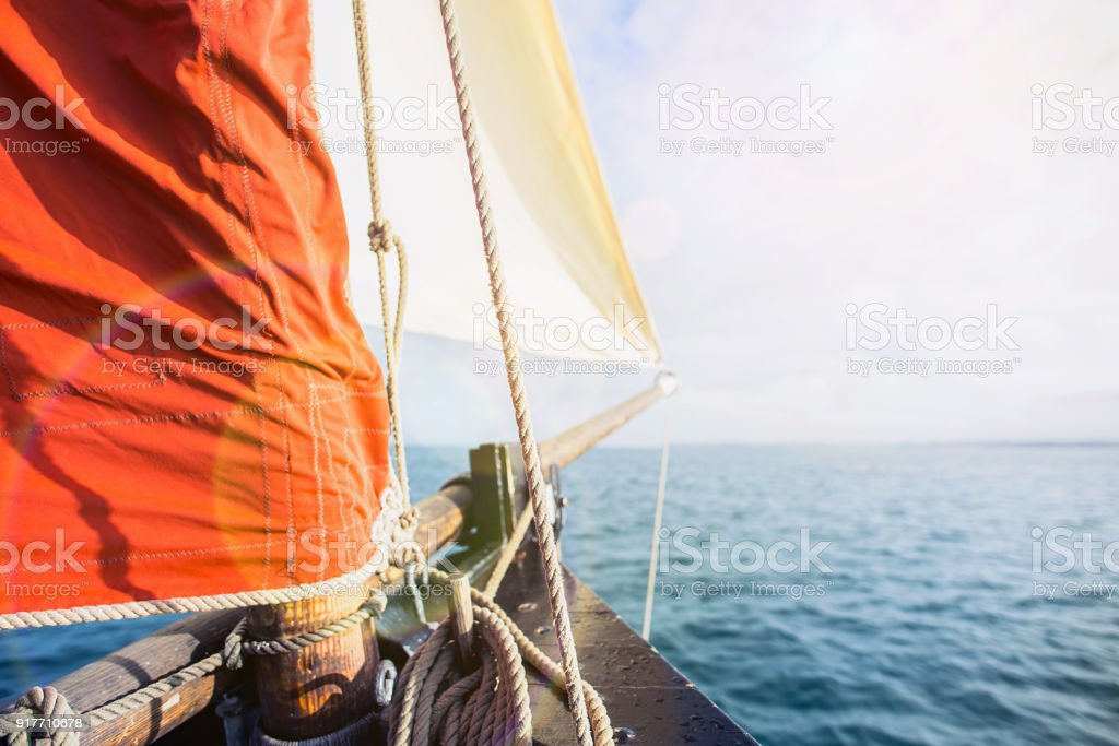 rope wound on a wooden cleat fixed on the hull of a rigging vintage sailing boat stock photo