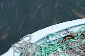 Detail of some green and gray ropes resting on a moored fishing boat.