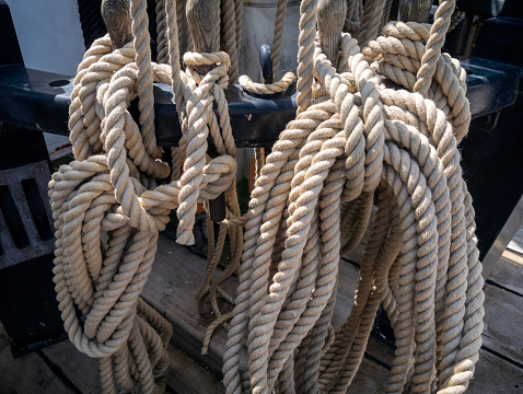 An assortment of ropes and stays, old and new, weathered and clean, by the deck of an old sailing ship.