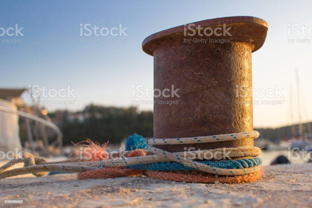 Ropes tied around a steel bollard stock photo