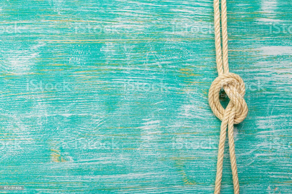 Ropes tied with knots on turquoise background stock photo