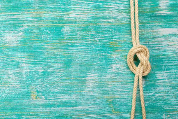seile mit knoten auf türkis hintergrund gebunden - horizontal gestreiften vorhängen stock-fotos und bilder