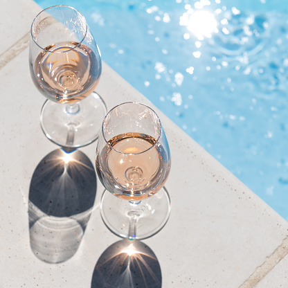 two glasses next to the pool in hard light
