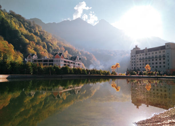 Rosa Khutor beach Panoramic scenic view of Rosa Khutor beach in Krasnaya polyana (Sochi, Russia). Water reflection of mountains and hotels in famous ski resort at summer autumn day sochi stock pictures, royalty-free photos & images
