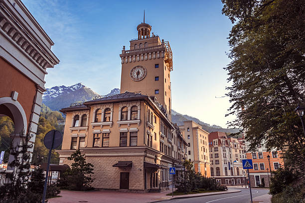 Rosa Khutor. Krasnaya Polyana. Sochi. Rosa Khutor. Krasnaya Polyana. Sochi. Historic building with the clock with a blue sky and mountains background and surrounded of the green trees / tourist attractions of Russia / unforgettable holiday in Krasnaya Polyana sochi stock pictures, royalty-free photos & images