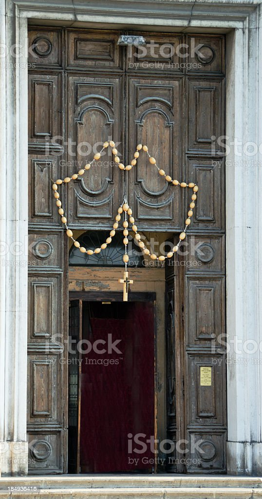 Rosary hanging above a large wooden church door. royalty-free stock photo