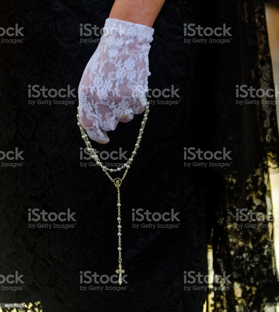 Rosary held by a woman in a black dress and white gloves, symbol of faith - Royalty-free Adult Stock Photo