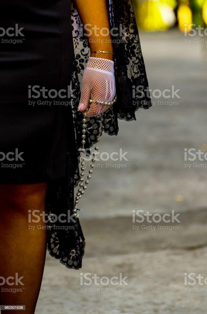 Rosário, realizado por uma mulher em um vestido preto e luvas brancas, símbolo da fé - Foto de stock de Adulto royalty-free