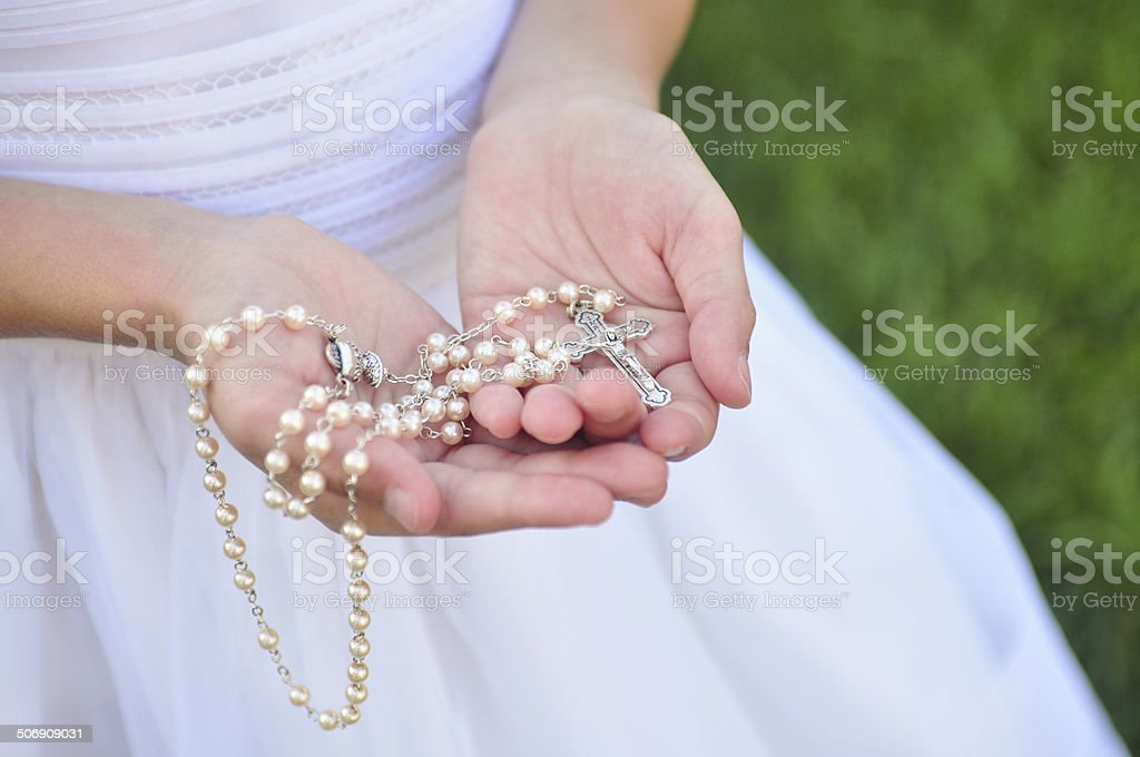 Rosary in Girl's hands stock photo