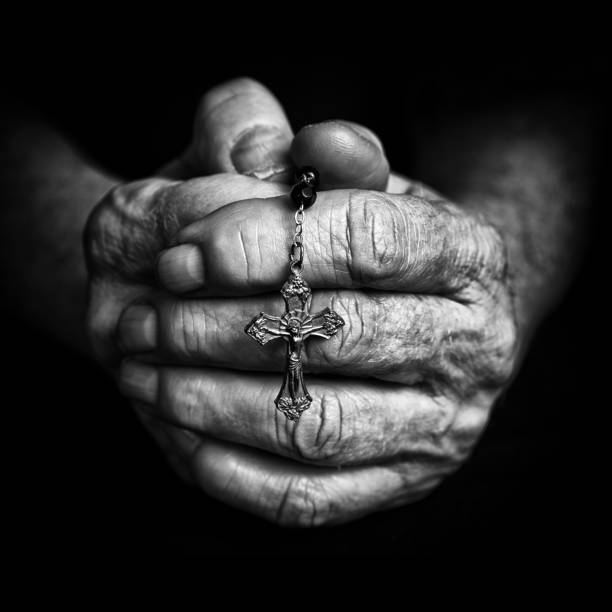 Rosary in praying hands stock photo