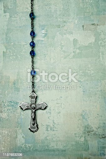 color image of a holy rosary against a textured backdrop